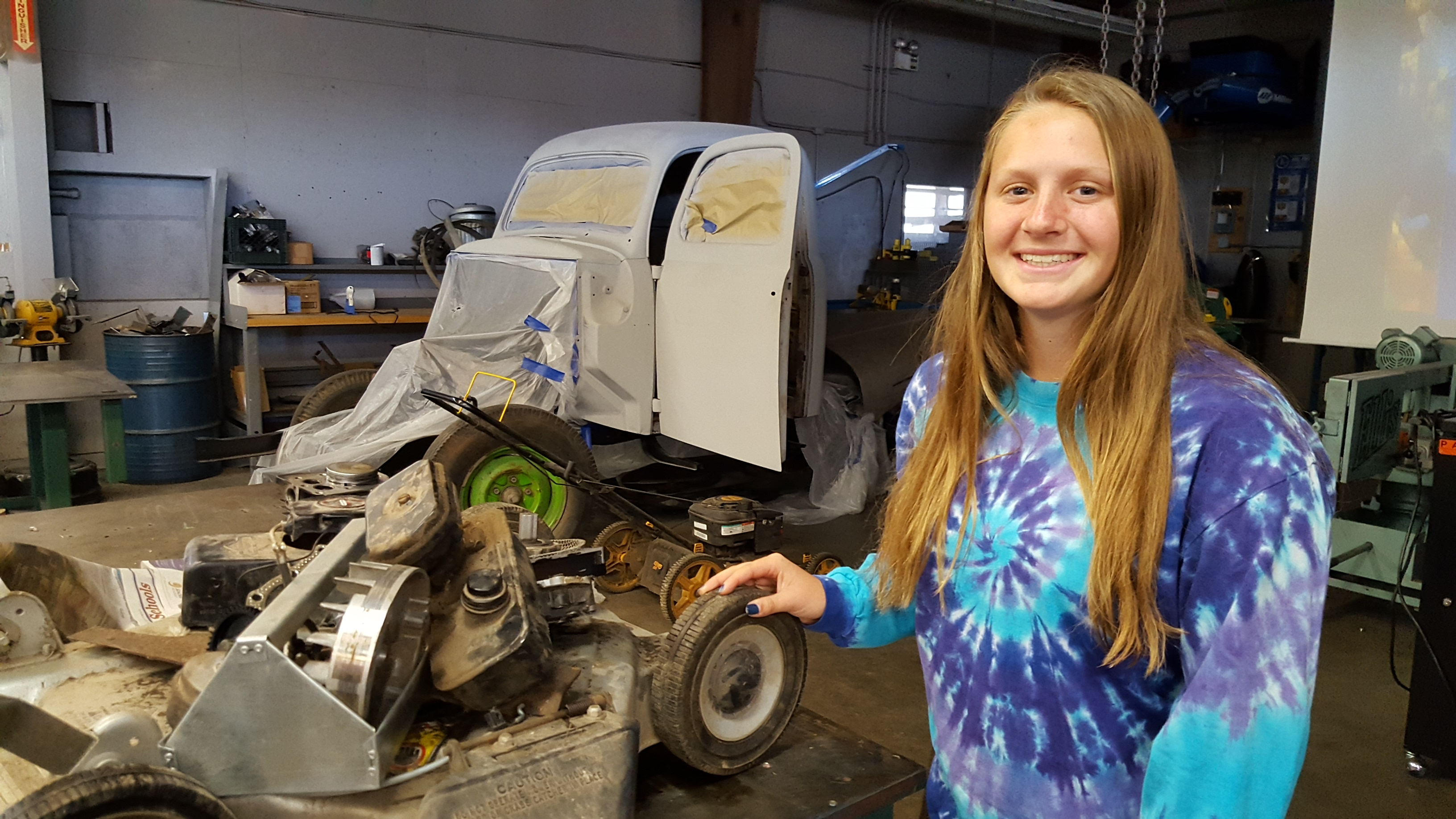 Student stands next to lawn mower in SVHS Power Mechanics class